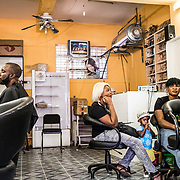 "Joseph (far left), a migrant from DRC, has been living in South Africa since 2004 and he is the manager of a hair salon in Yeoville. Hair salons have proliferated in the neighbourhood, and hair dresser is seen as a profitable activity in this area where migrants want to have their done by fellow country man and woman. Joseph lives and works in Yeoville, and admits he ""never goes anywhere else"". © Miora Rajaonary / Native Agency"
