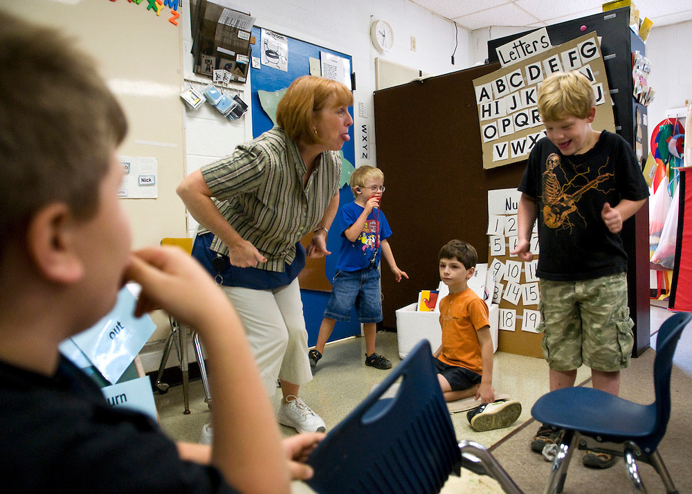 Anthony O'Rourke (right), 6, follows along with Lissa Riley during a song while other students watch. Riley's kindergarten class consists of eight rambunctious five- to seven-year-old boys..