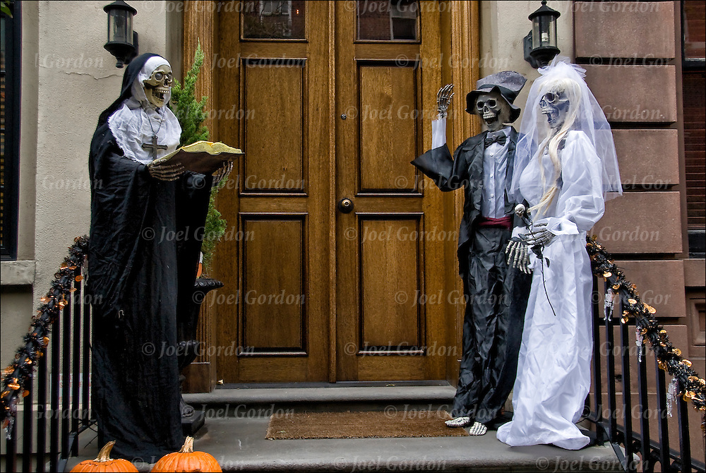 The groom says I do, Halloween decorations in Greenwich Village, plastic skeleton of nun with bible across from skeletons of bride and groom.