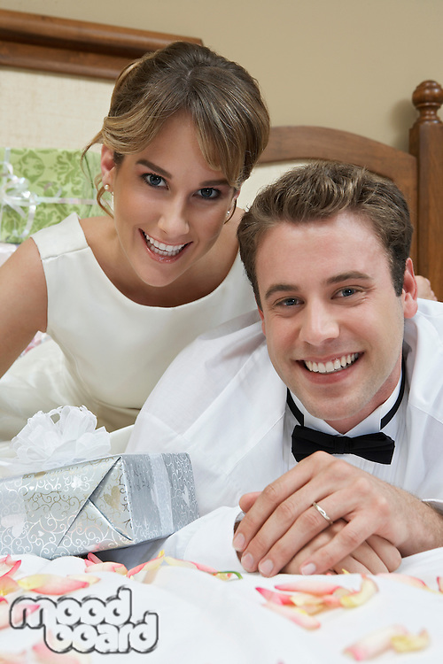 Bride and groom relaxing on bed among presents