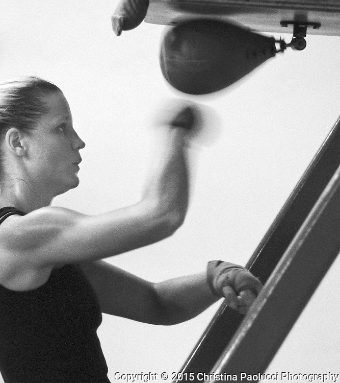 Lorie Mueller concentrates on the punching bag at the gym.