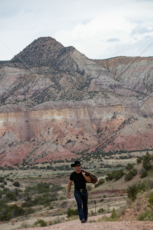 cowboy with a duffle bag over his shoulder walking on a mountain range