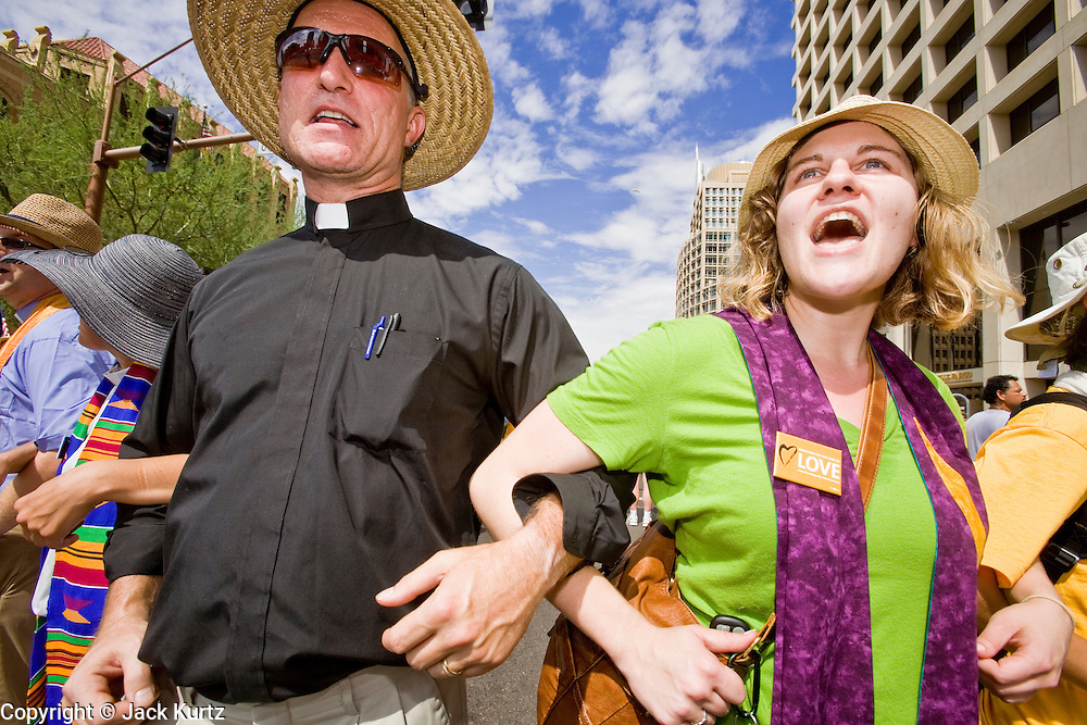 """29 JULY 2010 - PHOENIX, AZ: Unitarian Universalists from across the US block Washington Street in downtown Phoenix. Dozens of people were arrested during protests against SB 1070 across central Phoenix Thursday. US Judge Susan Bolton's ruling Wednesday stopped four of SB 1070's more than a dozen provisions from going into effect. She wrote, """"The court also finds that the United States is likely to suffer irreparable harm if the court does not preliminarily enjoin enforcement of these sections,"""" she states in the ruling. """"The balance of equities tips in the United States' favor considering the public interest.""""    PHOTO BY JACK KURTZ"""