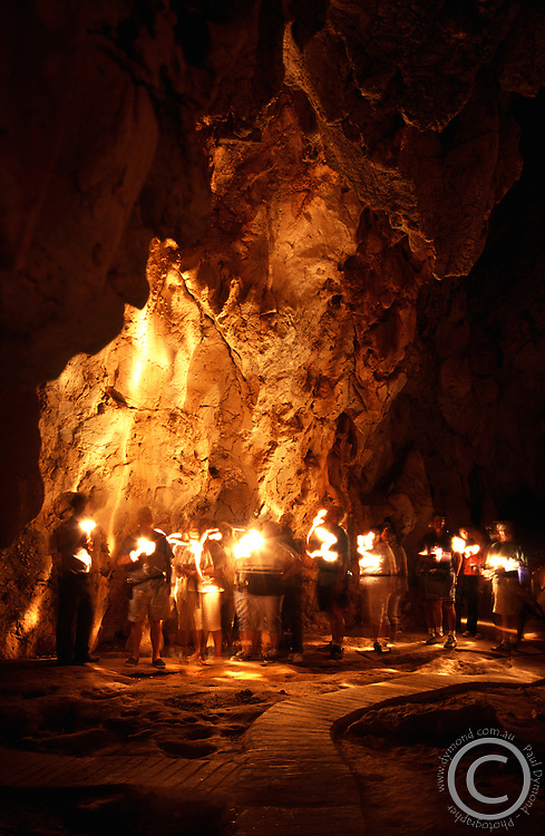 The inside of the Royal Arch Cave in Chillagoe National Park. The walls are illuminated by torches from a tour group.