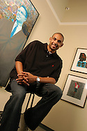 National Basketball Association player Grant Hill sits with some of his collection of African-American artwork on display at the Orlando Museum of Art in Orlando, Florida.