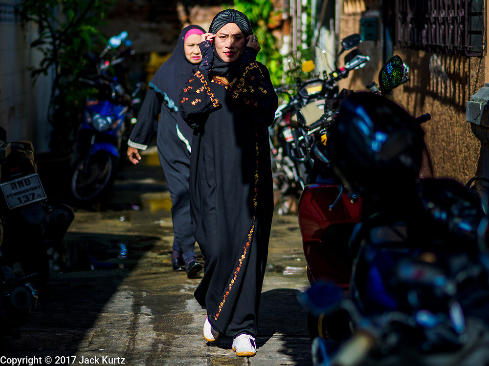 01 SEPTEMBER 2017 - BANGKOK, THAILAND: Women walk to mosque during the celebration of Eid al-Adha at Haroon Mosque in Bangkok. Eid al-Adha is also called the Feast of Sacrifice, the Greater Eid or Baqar-Eid. It honours the willingness of Abraham to sacrifice his son. Goats, sheep and cows are sacrificed in a ritualistic manner after services in the mosque. The meat from the sacrificed animal is supposed to be divided into three parts. The family retains one third of the share; another third is given to relatives, friends and neighbors; and the remaining third is given to the poor and needy.     PHOTO BY JACK KURTZ