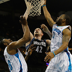 February 7, 2011; New Orleans, LA, USA; Minnesota Timberwolves power forward Kevin Love (42) shoots over New Orleans Hornets center D.J. Mbenga (28) and guard Marcus Thornton (5) during the third quarter at the New Orleans Arena. The Timberwolves defeated the Hornets 104-92.  Mandatory Credit: Derick E. Hingle