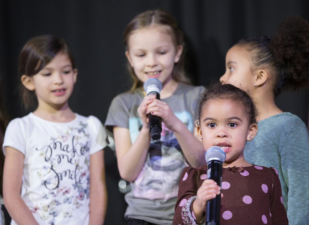 "Assistant Dean of Students Jamie Patton's daughters Eboni Patton, front, and Jazmine Patton, back right, and nieces Avi Figueroa, 7, back left, and Sara Figueroa, 9, back center, sing ""We are the World"" during the Faculty Pageant on February 22, 2016. Patton came in first place at the pageant."