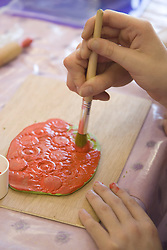 Close up of the hands of Service user with learning disability painting a piece of modeling clay,