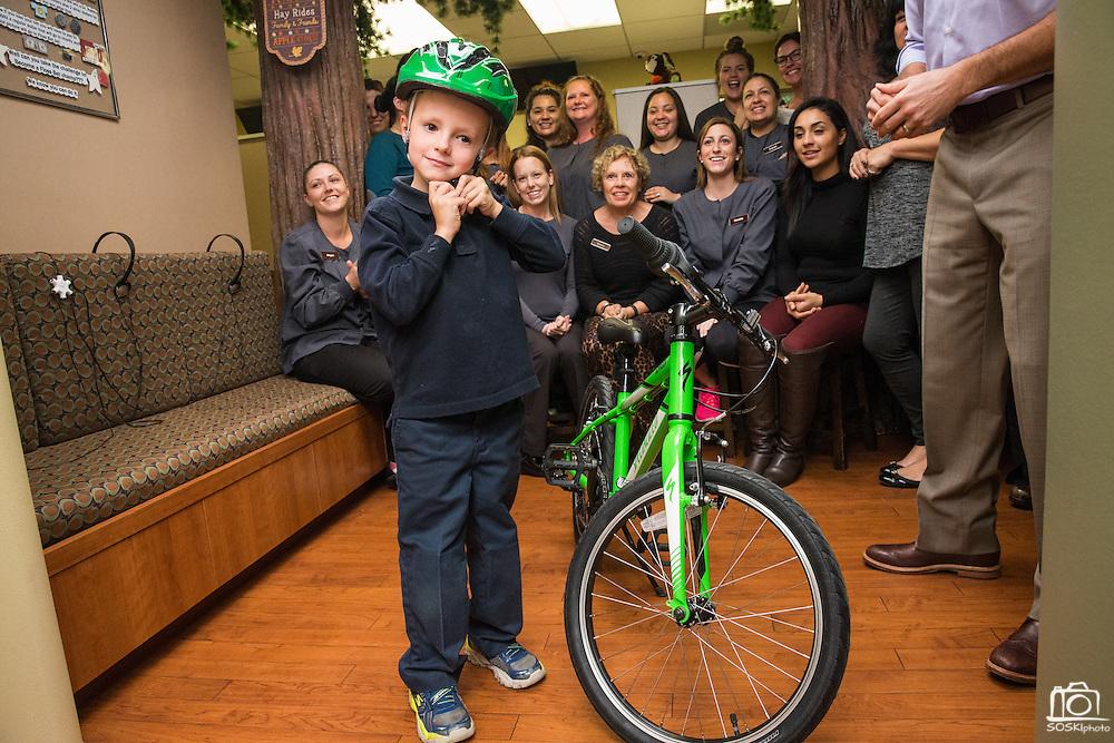 Annual Bicycle No Cavity winner receives his bike at Dr. Rabitz Pediatric Dentistry in San Jose, California, on November 14, 2016. (Stan Olszewski/SOSKIphoto)