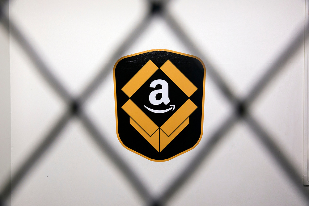 An Amazon.com logo is displayed behind a fence at the Amazon.com Inc. Prime Now fulfillment center warehouse on Monday, March 27, 2017 in Los Angeles, Calif. The warehouse can fulfill one and two hour delivery to customers. Complex supply chains such as Amazon's and e-commerce trends will impact city infrastructure and how things move through cities. © 2017 Patrick T. Fallon