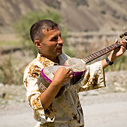 Tajik man playing traditional stringed musical instrument