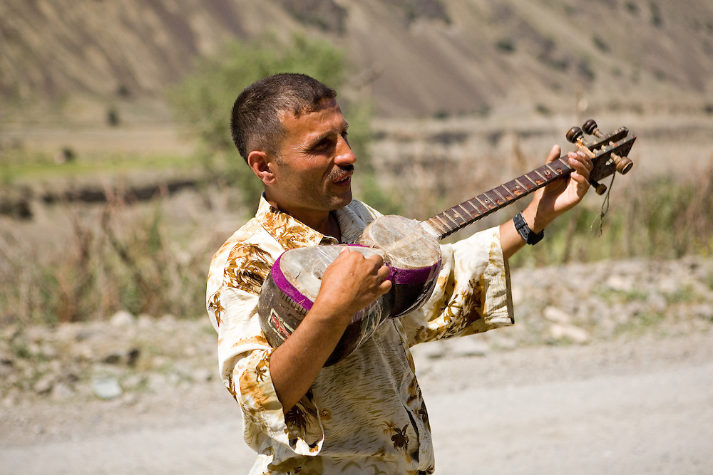 Tajik man playing traditional stringed musical instrument