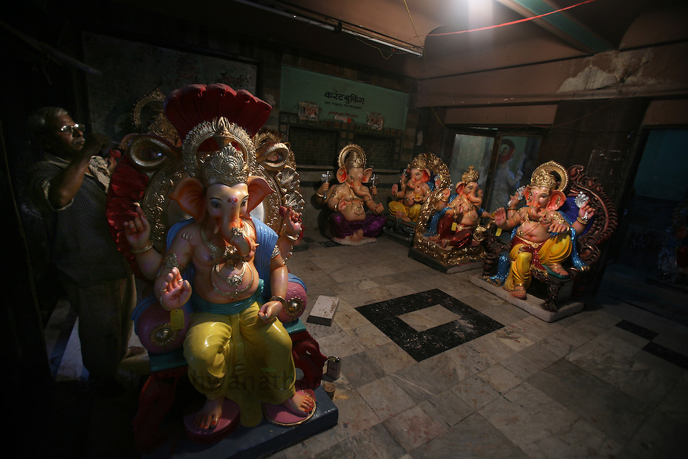 """A skilled labourer works on a unfinished Ganesha Idol in an closed down cinema theatre in Mumbai, September 6, 2007. Lord Ganesha idols are prepared for the """"Ganesh Chaturthi"""" (the Ganesh festival), a popular religious festival in India.Photographer: Prashanth Vishwanathan"""