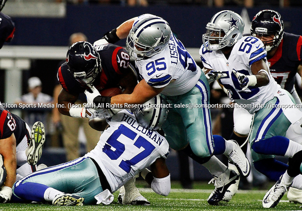 29 AUGUST 2013: Houston Texans running back Dennis Johnson (28) is tackled by Dallas Cowboys outside linebacker DeVonte Holloman (57) and Dallas Cowboys nose tackle Sean Lissemore (95) during a preseason NFL game between the Houston Texans and Dallas Cowboys at AT&T Stadium in Arlington, Texas.