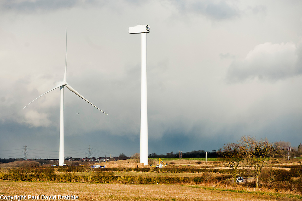 Ulley Wind Farm One completed Wind Turbine beside a second which is awaiting the its blades and hub to be assembled and hoisted into place. Note the comparative size of the yellow excavator at the foot of the un-finished turbine and the car in the bottom right hand corner for scale..13  March  2013.Image © Paul David Drabble