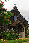 Christ Memorial Church, a stone church located in Kilauea, Kauai, Hawaii surrounded by tropical plants.