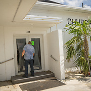 MARATHON, FL - SEPTEMBER 16: <br /> Tim Thompson, Minister of the Marathon Church of Christ, opens the front door to his church after arriving from Homestead where he and his wife evacuated to before Hurricane Irma made landfall. They rent a house next to the church on September 16, 2017 in Marathon, Florida.  (Photo by Angel Valentin/Getty Images)