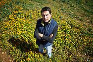 Putignano, Italia - 17 marzo 2012. Vincenzo Netti, 34 anni, ritratto nei campi che fanno parte della sua azienda (nella foto un campo di colza). Ha ereditato l'azienda agricola  del padre che ha poi trasformato in azienda agroenergetica: Vincenzo Netti, grazie all'utilizzo di pannelli solari, una piccola pala eolica e alla coltivazione della colza (piccola pianta dai fiori arancioni) produce energia e biocarburanti. La sua azienda e totalmente autosufficiente dal punto di vista energetico..Ph. Roberto Salomone Ag. Controluce.ITALY - Vincenzo Netti, 34, portrayed on the terrains of his company in Putignano (Bari) on May 17, 2012. Vincenzo Netti produces biofuel by harvesting the colza plant. His company is totally independent from an energetic point of view since he uses solar panels and mini aeolic shovel.