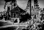 After making offerings, a woman leaves Pura Ulun Danu Batur which was moved up onto the lofty outer rim of the Batur Caldera from inside the caldera after the original temple, and Batur village, were destroyed by two volcanic eruptions in 1917 and 1926.  Bali, Indonesia.