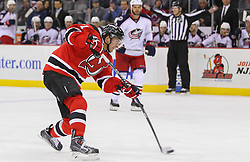 Feb 27, 2014; Newark, NJ, USA; New Jersey Devils center Andrei Loktionov (21) shoots the puck during the first period of their game against the Columbus Blue Jackets  at Prudential Center.