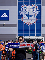 CARDIFF, WALES - Saturday, April 20, 2019: A supporter poses for a photograph with a half-and-half scarf ahead of the FA Premier League match between Cardiff City FC and Liverpool FC at the Cardiff City Stadium. (Pic by David Rawcliffe/Propaganda)