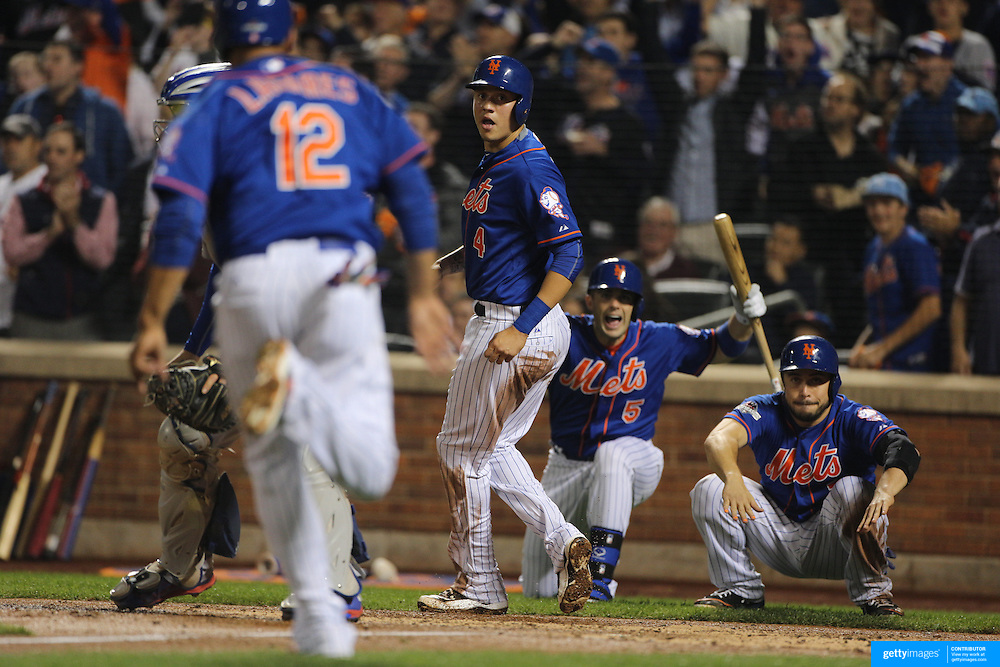Juan Lagares, New York Mets, is encouraged by Wilmer Flores, David Wright and Travis d'Arnaud as he heads home on a three run double by Curtis Granderson, during the New York Mets Vs Los Angeles Dodgers, game three of the NL Division Series at Citi Field, Queens, New York. USA. 12th October 2015. Photo Tim Clayton for The Players Tribune
