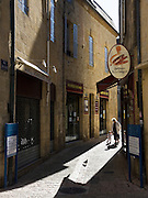 Late afternoon street scene with a grandmother and grandchild on a stroll in the town of Sarlat la Caneda, Dordogne, France.