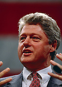 President Bill Clinton while speaking. A large American flag hangs behind him.