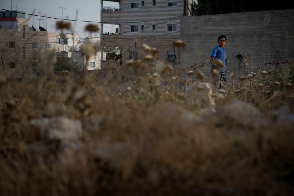 A child plays on the outskirts of Aida refugee camp near the town of Bethlehem, West Bank, Wednesday 14th May 2008.