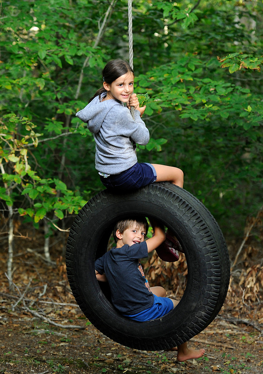 WOODS HOLE -- 081513 -- Aline Waldhauser, 6, and her brother Nico, 4, play on the tire swing behind their family's MBL cottage.  Christine Hochkeppel/Cape Cod Times