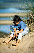 Young girl sits on a sand dune. Lonely, summer, Cape Cod, vacation, seven.