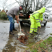Tupelo Public Works employees Trent Hutcherson and Brad Richey remove built up debris at a drainage opening on Houston Street to releave the street from holding water during the rain on Wednesday morning.