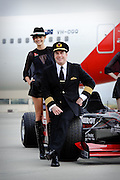 John Travolta addresses the media reception at Melbourne International airport after landing to attend the Formula One Grand Prix as an ambassador at large for Qantas. Behind Mr. Travolta is Qantas model Emily Cattermole...Photo by Mark Tantrum.