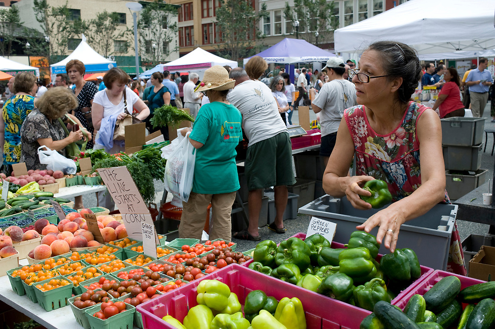 Allison Crispin, right, of Harvest Valley Farms, stocks green peppers between waiting on customers at the Market Square Farmers Market in downtown Pittsburgh.  The Farmers Market is held every Thursday until November.