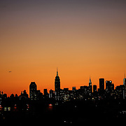 The sun sets behind the Manhattan skyline as a plane passes over the City viewed from Arthur Ashe Stadium  during the US Open Tennis Tournament, Flushing, New York. USA. 10th September 2012. Photo Tim Clayton