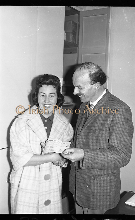 Gael Linn Bingo..1963..03.10.1963..10.03.1963..3rd October 1963..Gael Linn bingo took place in Whitehall Cinema last night, it set a record when Mrs Kathleen Sperrin from Swords Road, Dublin filled a line in only 8 calls. This achievement completed in a time of only 30 seconds won a bonus prize of £100 for Mrs Sperrin in addition to the ordinary prize...Image of Mrs Kathleen Sperrin from Swords who won the bonus prize of £100 for successfully completing a line in only eight calls. Mr Donal Ó Móráin of Gael Linn is pictured presenting the bonus cheque.