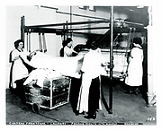 Laundry room of the Chateau Frontenac with women feeding sheets into a mangle, photograph, from the Archives of the Chateau Frontenac, Quebec City, Quebec, Canada. The Chateau Frontenac opened in 1893 and was designed by Bruce Price as a chateau style hotel for the Canadian Pacific Railway company or CPR. It was extended in 1924 by William Sutherland Maxwell. The building is now a hotel, the Fairmont Le Chateau Frontenac, and is listed as a National Historic Site of Canada. The Historic District of Old Quebec is listed as a UNESCO World Heritage Site. Copyright Archives Chateau Frontenac / Manuel Cohen