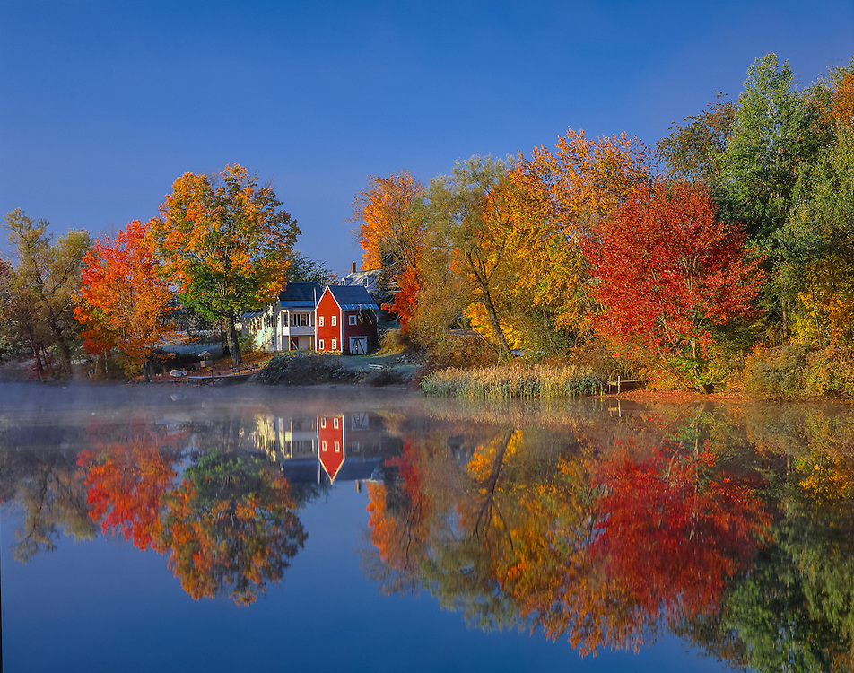 Red barn and white house with fall foliage trees reflected in pond, misty fog rising, East Andover, NH