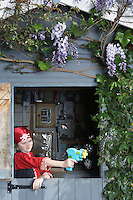 Young boy (7-9) in pirate costume aiming with toy gun from shed