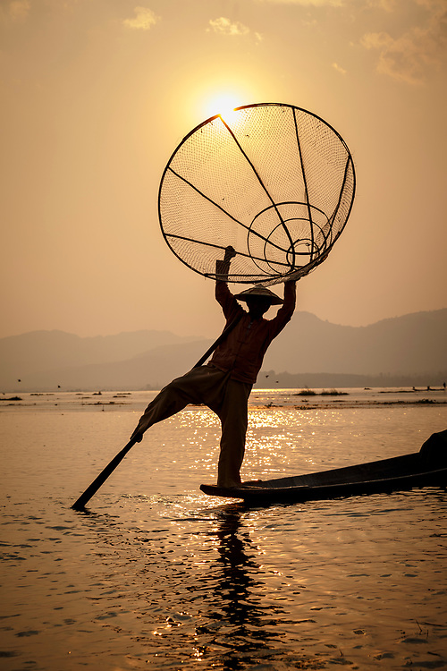 Sunset fisherman with his net catching the sun, on Lake Inle, Shan State, Myanmar