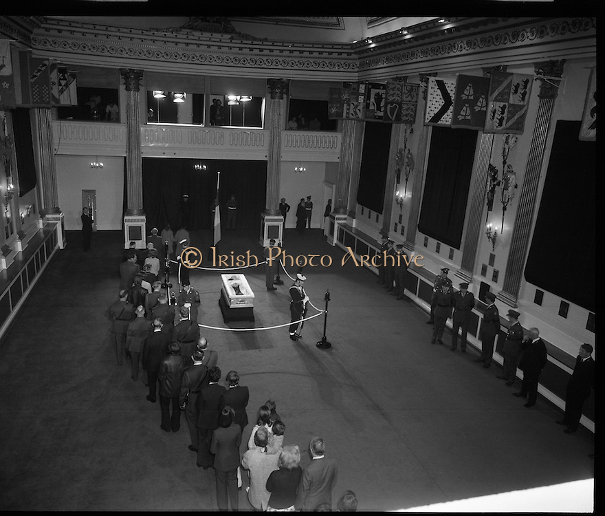 Eamon DeValera Lies in State.   (J72)..1975..31.08.1975..08.31.1975..31st August 1975..Following his death, Eamon DeValera lay in state at Dublin Castle. Following President Cearbhaill O'Dalaigh,Taoiseach Liam Cosgrave,Fianna Fail leader, Jack Lynch and members of the Dail and Seanad the hall was opened to the public so that they could pay their respects...Image shows the coffin, containing the remains of the late Eamon DeValera, with guard of honour being passed by members of the public as they pay their respects.