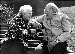Elderly couple sitting on bench holding hands and laughing,