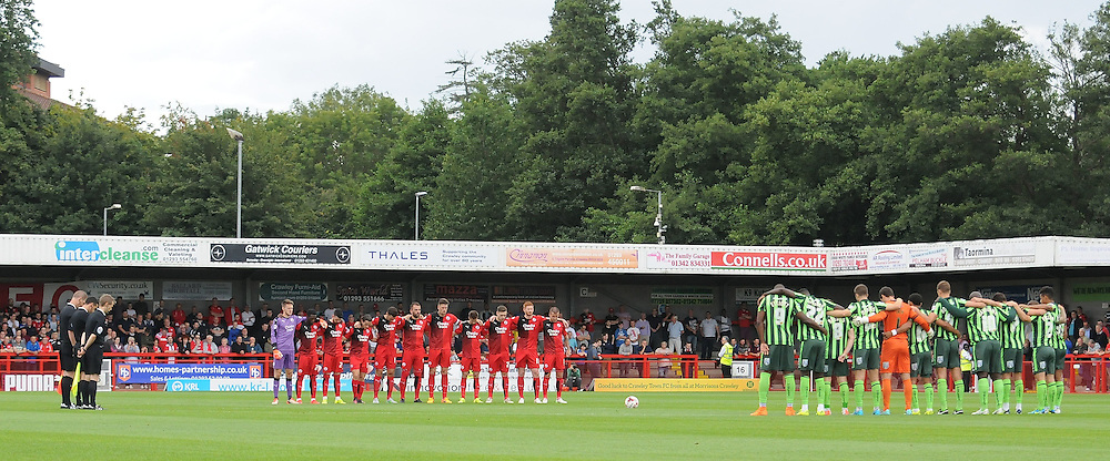 Both sets of players observe a minute's silence before the Sky Bet League 2 match between Crawley Town and AFC Wimbledon at the Checkatrade.com Stadium, Crawley, England on 15 August 2015. Photo by Michael Hulf.