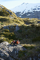 Two hikers sitting on boulders in mountain valley