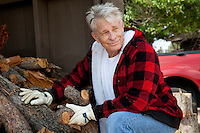 Senior man sitting besides firewood log