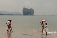 Chinese tourists on Sanya beach, with the construction for a new marina at the horizon.