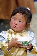 GOBI DESERT, MONGOLIA..08/26/2001.Bayangovi. Girl at local Naadam festival with bowl of mares' milk..(Photo by Heimo Aga).