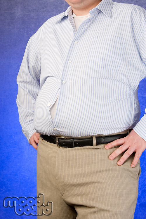 Overweight Man standing with unbuttoned shirt, hands on hip, mid section