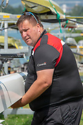 Lucerne, SWITZERLAND, 12th July 2018, Thursday,  FISA World Cup Regatta III, Lake Rotsee, Lucerne, New Zealander, Dave THOMPSON, Working as a coach with Rowing Canada, moving a boat on the rack,